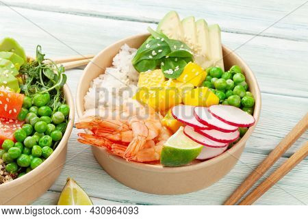 Poke bowls with shrimps, salmon, avocado and mango. Traditional hawaiian meal
