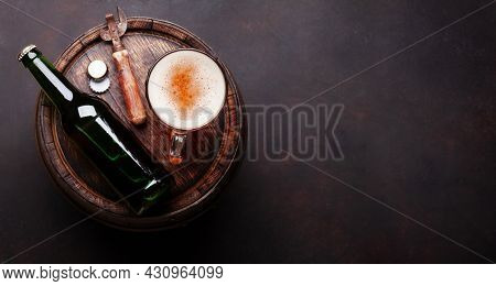 Lager beer mug, bottle and bottle opener on old wooden barrel. Top view flat lay with copy space