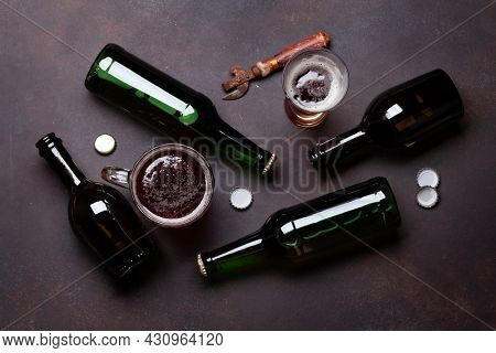 Beer bottles, lager beer glass and mug, bottle opener. Top view flat lay
