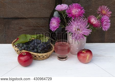 On The Table There Is A Bouquet Of Bright Flowers Of Asters, A Glass Of Wine, A Bunch Of Grapes And