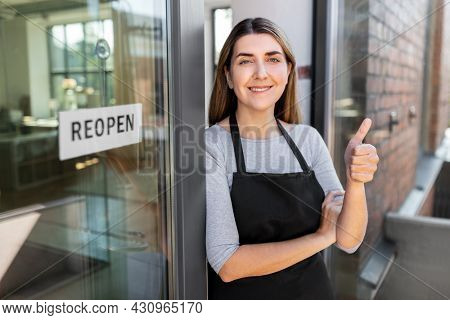 small business, reopening and service concept - happy smiling woman with reopen banner on window or door glass showing thumbs up
