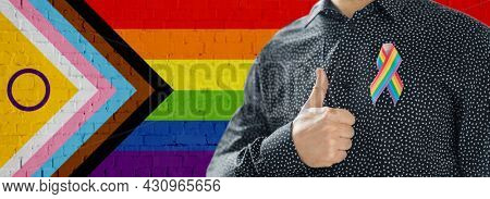 lgbtq, trans and intersex rights concept - close up of man wearing gay pride awareness ribbon showing thumbs up over rainbow progress flag background