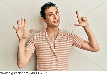 Handsome man wearing make up wearing casual t shirt showing and pointing up with fingers number seven while smiling confident and happy.