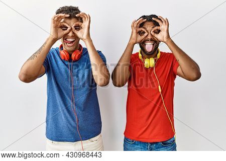 Young hispanic brothers standing over isolated background wearing headphones doing ok gesture like binoculars sticking tongue out, eyes looking through fingers. crazy expression.