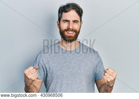 Caucasian man with beard wearing casual grey t shirt excited for success with arms raised and eyes closed celebrating victory smiling. winner concept.