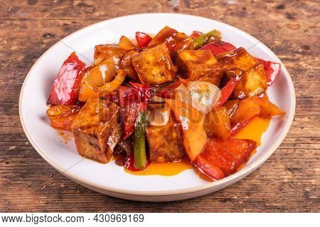 Tofu Stewed With Peppers And Onions In Sweet And Sour Sauce On A Plate Close-up