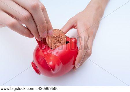 Hand Putting Bitcoin Coin Into A Red Piggy Bank, Close-up. Bitcoin Electronic Money Saving Concept.