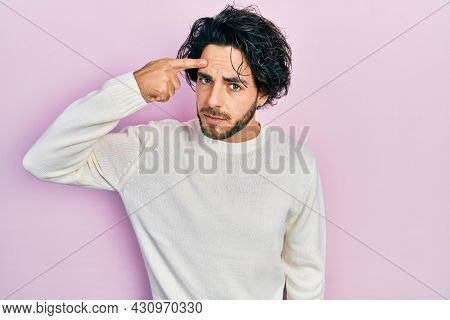 Handsome hispanic man wearing casual white sweater pointing unhappy to pimple on forehead, ugly infection of blackhead. acne and skin problem