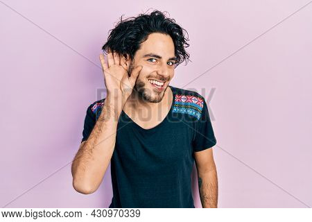 Handsome hispanic man wearing casual t shirt smiling with hand over ear listening and hearing to rumor or gossip. deafness concept.