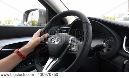 Unrecognizable Man Holding Hand On Steering Wheel Of Infiniti Qx50 And Driving Car By Highway. Male