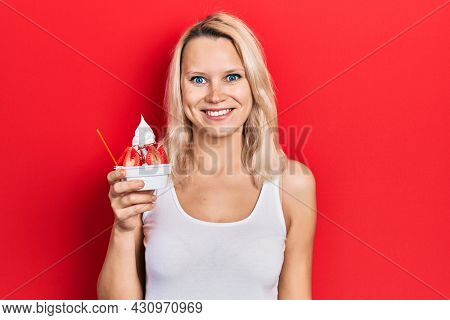 Beautiful caucasian blonde woman eating strawberry ice cream looking positive and happy standing and smiling with a confident smile showing teeth