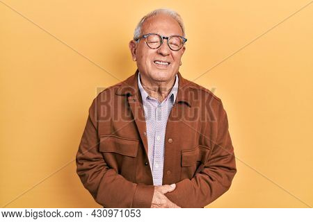 Senior man with grey hair wearing casual jacket and glasses with hand on stomach because indigestion, painful illness feeling unwell. ache concept.