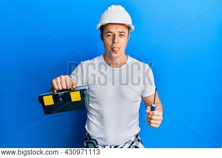 Handsome young man holding toolbox and screwdriver sticking tongue out happy with funny expression.