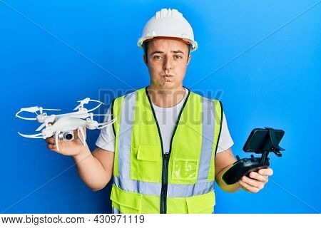 Handsome young man wearing safety hard using drone and control puffing cheeks with funny face. mouth inflated with air, catching air.
