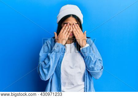 Young latin woman wearing cute wool cap rubbing eyes for fatigue and headache, sleepy and tired expression. vision problem