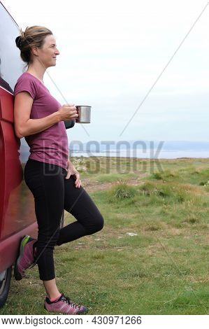 Woman Holding A Cup In Her Hand Next To Her Campervan On Her Summer Holiday.