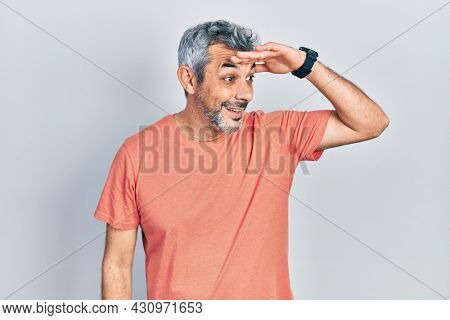 Handsome middle age man with grey hair wearing casual t shirt very happy and smiling looking far away with hand over head. searching concept.