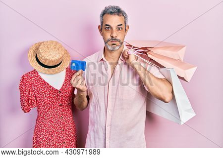 Handsome middle age man with grey hair holding shopping bags and credit card puffing cheeks with funny face. mouth inflated with air, catching air.