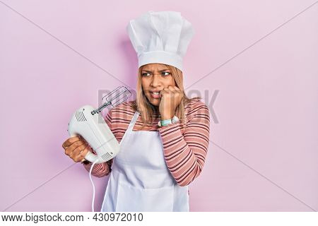 Beautiful hispanic woman holding pastry blender electric mixer looking stressed and nervous with hands on mouth biting nails. anxiety problem.