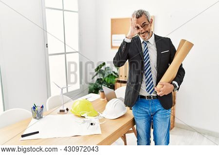 Middle age hispanic business man holding paper blueprints doing ok gesture with hand smiling, eye looking through fingers with happy face.