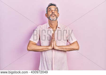 Handsome middle age man with grey hair wearing casual shirt begging and praying with hands together with hope expression on face very emotional and worried. begging.