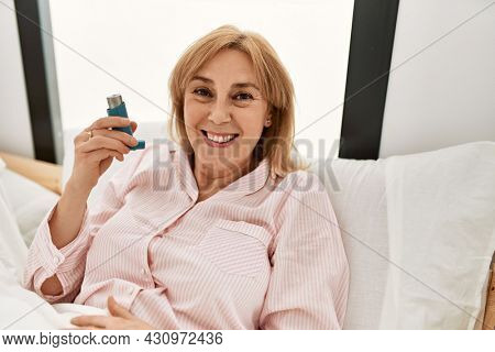 Middle age asthmatic woman smiling happy using inhaler lying on the bed at home.