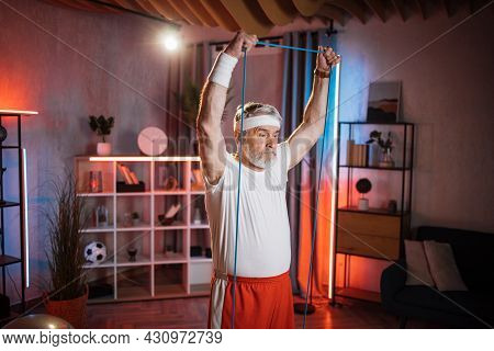 Grey Haired Caucasian Man Wearing Sport Clothes And Headband Having Domestic Workout With Rubber Ban