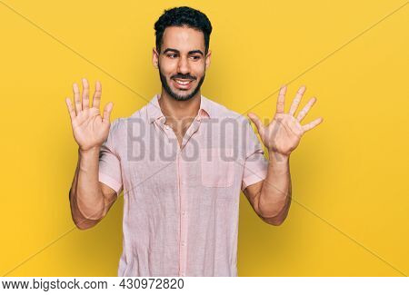 Hispanic man with beard wearing casual shirt showing and pointing up with fingers number ten while smiling confident and happy.