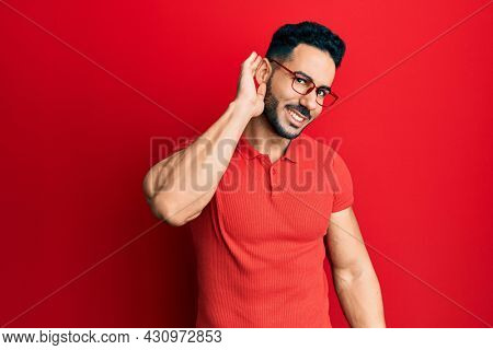 Young hispanic man wearing casual clothes and glasses smiling with hand over ear listening an hearing to rumor or gossip. deafness concept.