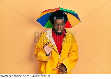 Young african american man wearing yellow raincoat disgusted expression, displeased and fearful doing disgust face because aversion reaction.