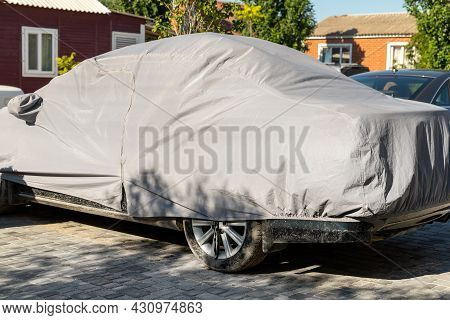 Many Cars Parked Near Suburban Home Driveway Covered With Protective Tarpaulin Cloth Cover To Protec