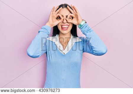Beautiful woman with blue eyes standing over pink background doing ok gesture like binoculars sticking tongue out, eyes looking through fingers. crazy expression.
