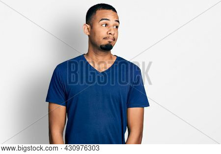 Young african american man wearing casual t shirt smiling looking to the side and staring away thinking.