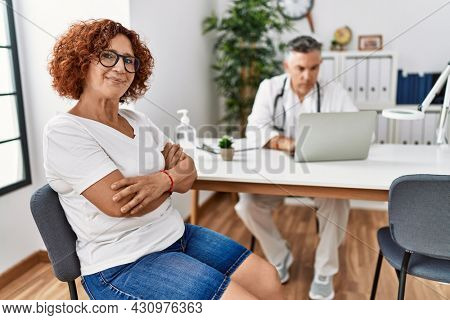 Senior woman sitting at doctor appointment smiling looking to the side and staring away thinking.