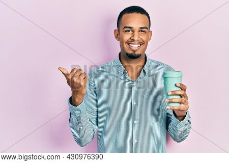 Young african american man drinking a take away cup of coffee pointing thumb up to the side smiling happy with open mouth