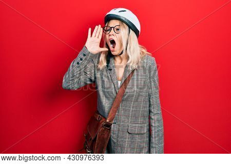 Beautiful caucasian blonde business woman wearing bike helmet shouting and screaming loud to side with hand on mouth. communication concept.