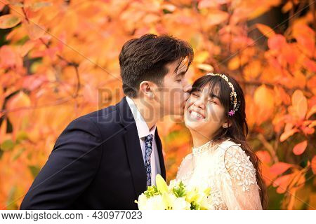 Biracial Newly Married Couple Kissing Outdoors By Bright Orange Autumn Leaves