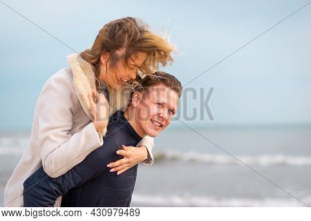 Happy Man Giving Piggyback Ride To His Woman And Laughing At A Beach. Smiling Guy In Love Carrying O