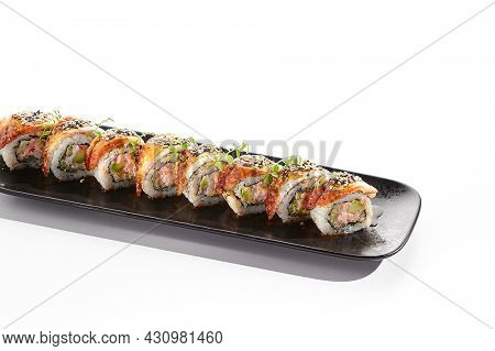 International sushi roll topped with smoked eel and sesame seed. Sushi roll with avocado and crab meat inside. Black slate sushi plate isolated on white background. Delicious sushi restaurant menu