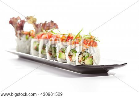 Healthy vegetarian Japanese lunch. Vegan sushi roll with avocado and mushrooms inside. Topped with tomato. Vegetarian sushi rolls dish. Restaurant asian vegan food isolated on white background