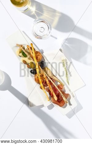 Appetizer wine set with wine bottle and glass. Fancy dinning with white wine and snack set on white table with simple contemporary decor. Sunlight and harsh shadow still life. Wine starter set