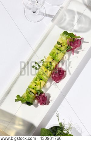 Avocado roll with crab meat inside on white plate. Healthy food keto diet. Ketogenic diet avocado food. Delicious restaurant dish with avocado in harsh lights