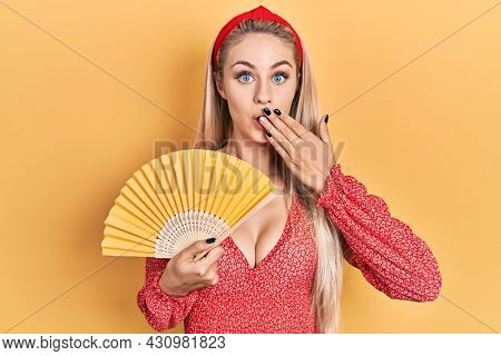 Young caucasian woman waving hand fan cooling air in summer covering mouth with hand, shocked and afraid for mistake. surprised expression