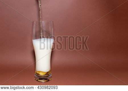 Beer Pouring From Bottle Into Glass.frothy And Amber Brilliance Craft Beer, Pouring In The Glass Wit