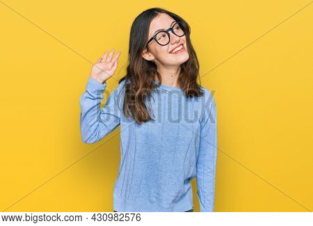 Young beautiful woman wearing casual clothes and glasses waiving saying hello happy and smiling, friendly welcome gesture