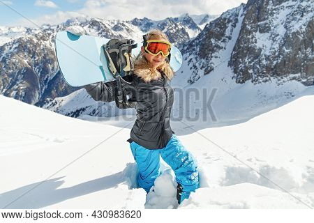 Portrait Of Beautiful Snowboarder Female Going To Freeride In Winter Mountain High. Sunny Winter Hol
