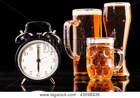 time to drink beer. glasses of fresh lager beer with clock on black with reflection