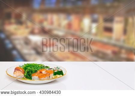 Table Top On Seafood Background. Closeup Of Various Kinds Of Sushi And Fresh Seaweed Salad On Plate
