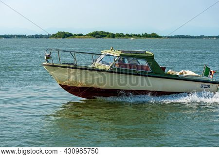 Venice, Italy - June 2, 2021: Small Speed Boat With One Person On Board Moving In The Venetian Lagoo