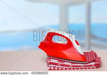 Closeup Of A Red Iron On A Stack Red And White Checkered Towels On Table Against An Abstract Bright